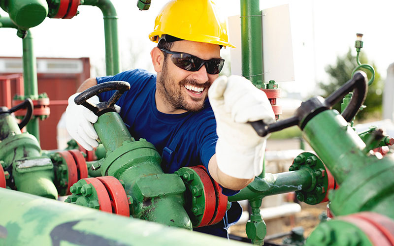 Smiling Man at Work Wearing Safety Glasses, Gloves, and Hard Hat