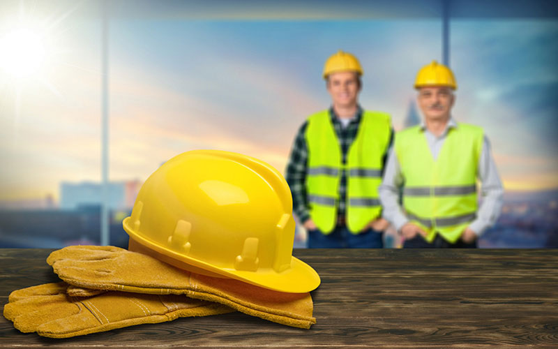 A Yellow Hard Hat Sitting on a Pair of Gloves